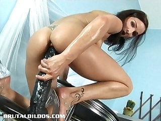 Petite brunette filling her tight pussy with a giant dildo